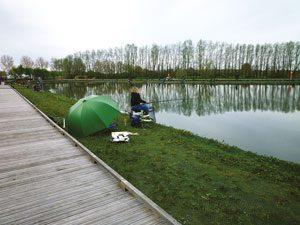 Un pêcheur au bord de l'étang de pêche